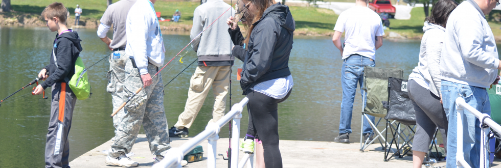 group of participants in the Bass Fishing Tournament fishing off the platform at Lake Side