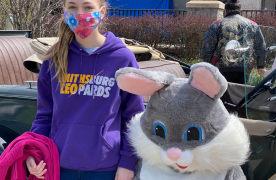 Young girl with purple sweatshirt standing next to the Easter Bunny
